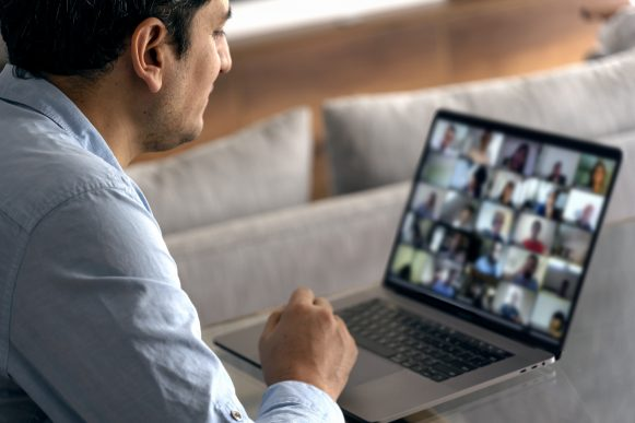 Man in a video conference with his team. Working at home with a laptop.
