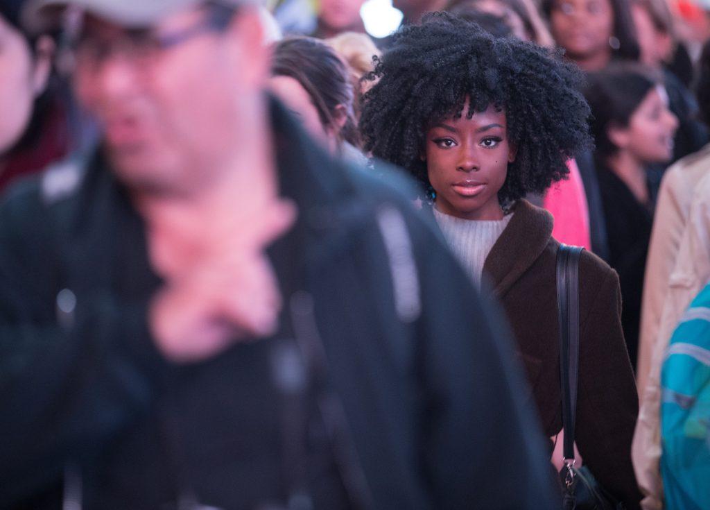 Pretty African American woman on a crowded city sidewalk